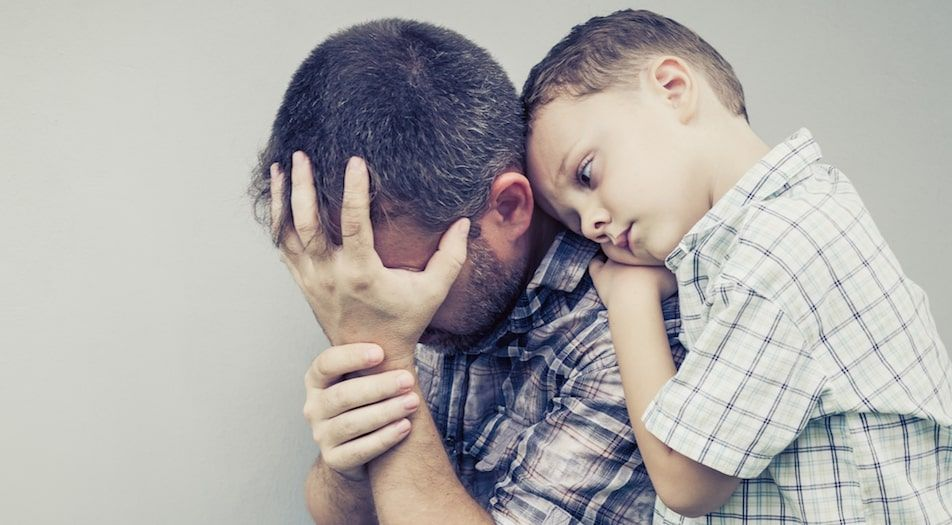 Son Hugging a dad feeling guilty