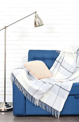A blue couch with a plaid blanket - the perfect seat for an individual psychotherapy session with Lauren Rosen, LMFT.