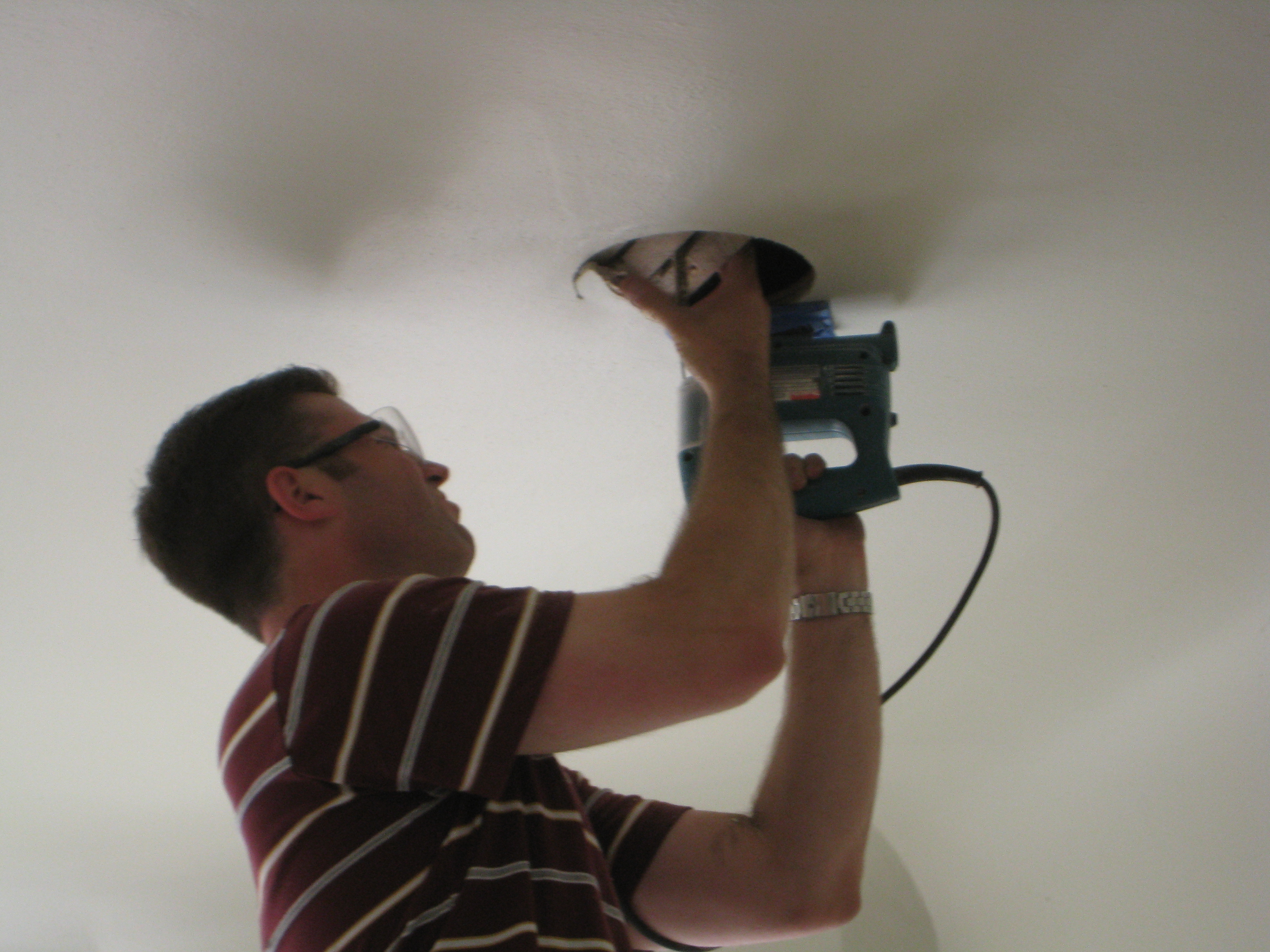 Cutting speaker holes in ceiling.