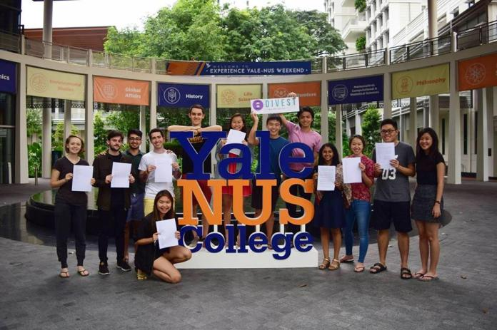 Yale-NUS Divest poses at in the oculus, at the entrance to Yale-NUS College, with copies of their petition.