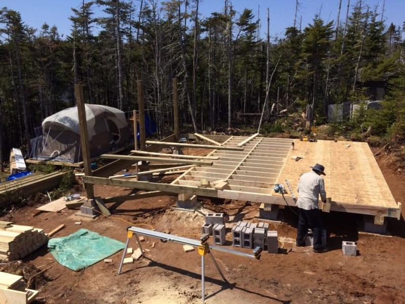 off grid cabin subfloor sheets being installed