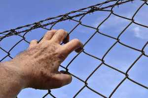 Hand on chain link fence with barbed wire at http://theolddirtroad.com