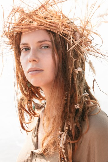 Close up Young Woman in Boho Style with Dreads Wearing Crown of Hay While Looking at the Camera.