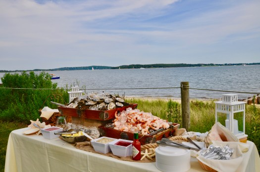 A seafood table piled high with shrimp, oysters, and clams over looking the bay water