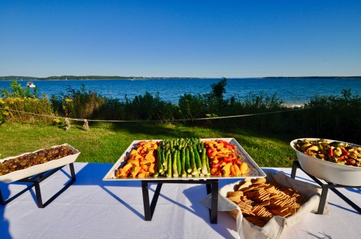 Vegetables, olives, salad, and crackers on a white table overlooking the bay water.