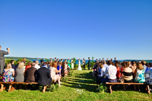 Wedding ceremony with couple and guests sitting on benches overlooking the bay.