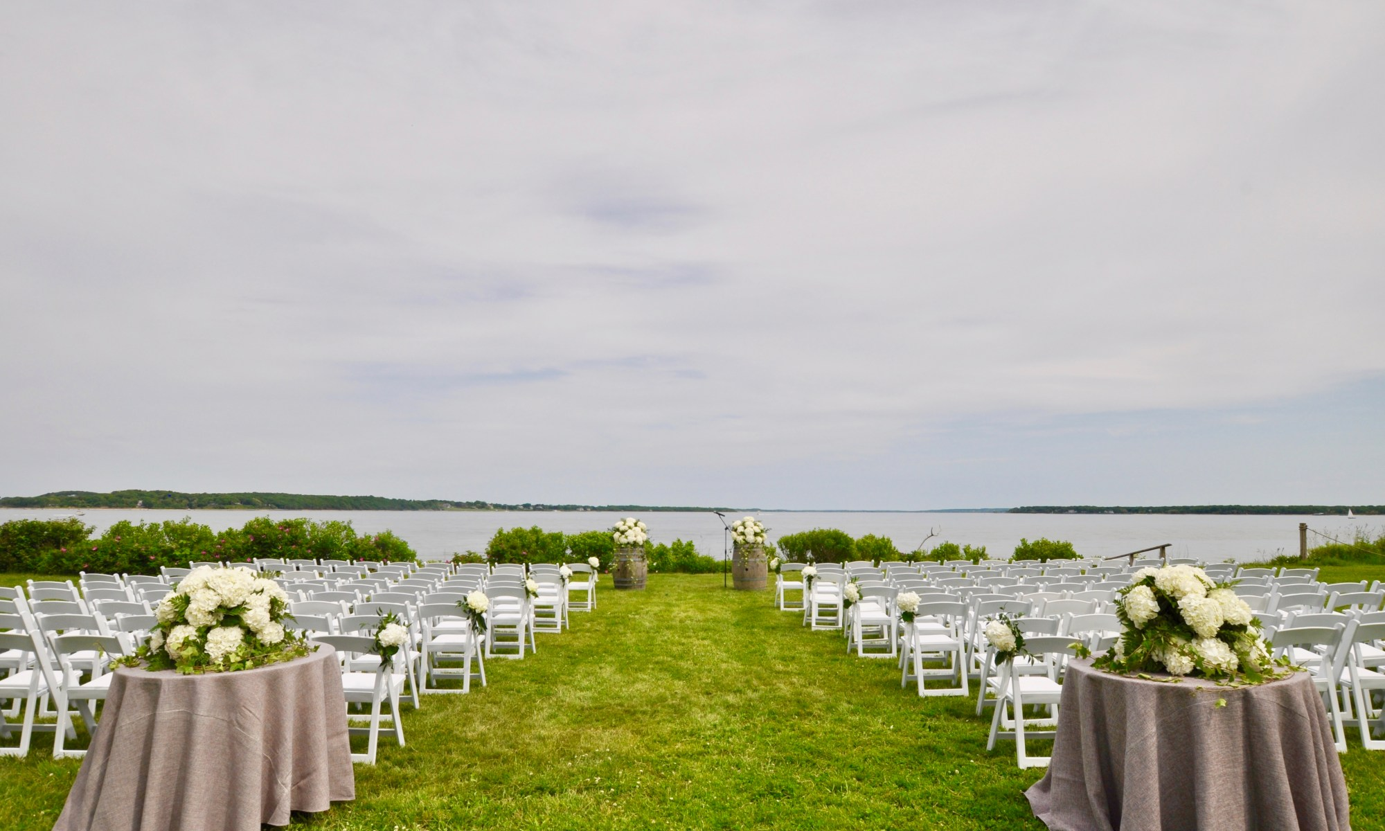 An isle with rows of white chairs on a green lawn overlooking Peconic Bay with flowers
