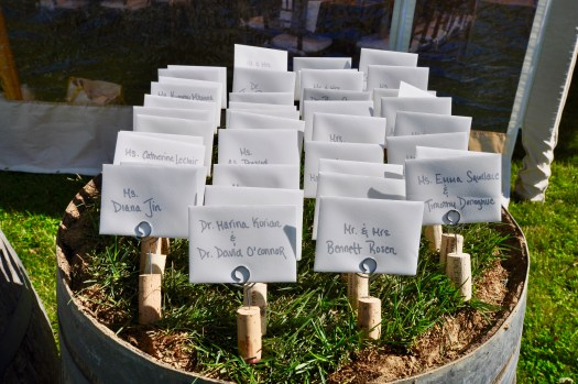 Place cards set in corks and planted in grass on a wine barrel.