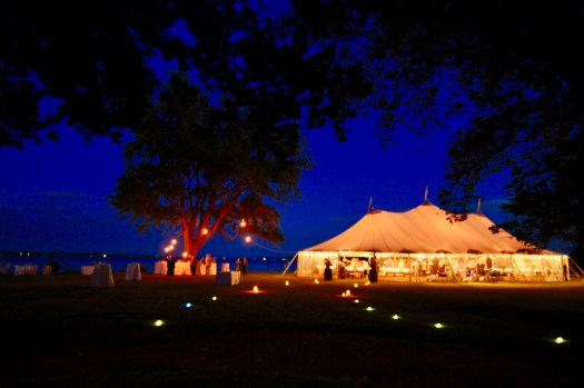 Night time scene with lit and glowing tent at the end of candle lit pathway. Bay in background and maple tree with bar set up under it.