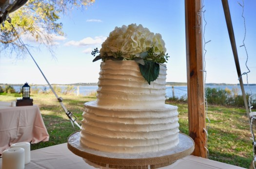Two tiered white wedding cakes topped with a white hydrangea.