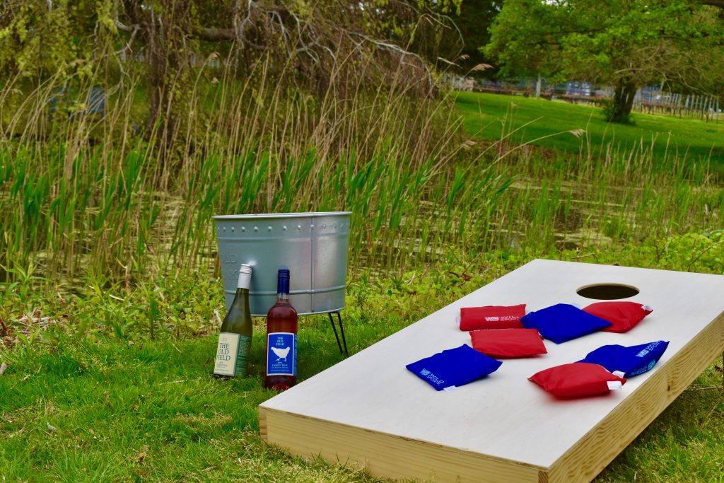 Corn hole with bottles and chill bucket next to board