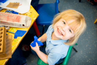 Short haired girl laughing to camera with a blue toy The Old Station Nursery in Dromore