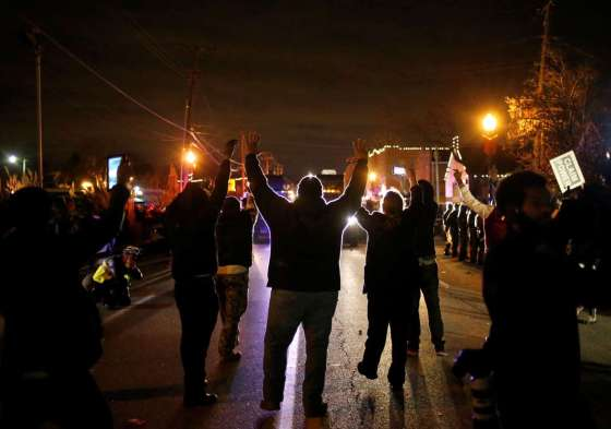 Protesters in Ferguson approach a police line with their hands up after the grand jury decision. © Adrees Latif/Reuters