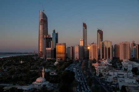 Another view from the balcony of my old apartment in Abu Dhabi, as the sun goes down behind it, reflecting off the plate glass of the office buildings. Note the traffic jam.