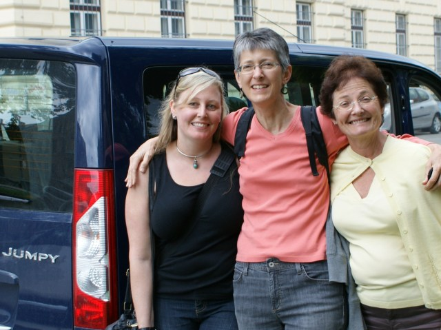 Going on a trip with your girl or guy friends to do something is a great gift as evidenced by the big smiles on three women in front of a van.