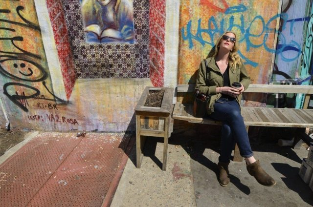 blonde woman with sunglasses and coffee in front of graffiti in the sunshine