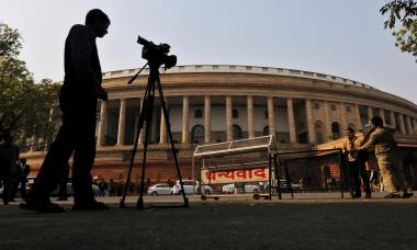 FILE PHOTO: Television journalists report from the premises of India's Parliament in New Delhi