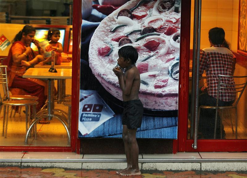 Homeless boy holds biscuits that he received as alms as he takes shelter from rain in Mumbai