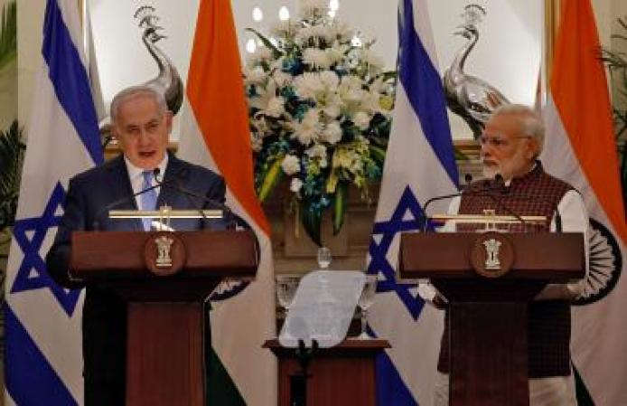 Israeli Prime Minister Netanyahu speaks as his Indian counterpart Modi looks on during a signing of agreements ceremony at Hyderabad House in New Delhi