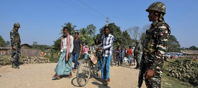 Villagers walk past CRPF personnel patrolling a road ahead of the publication of the first draft of the National Register of Citizens in the Juria village of Nagaon district