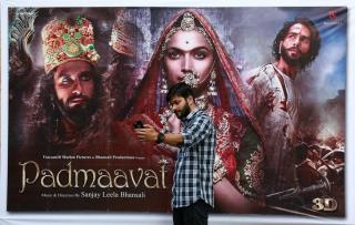 "A cinemagoer takes a selfie in front of a poster of Bollywood movie ""Padmaavat"" outside a movie theatre in Kochi"