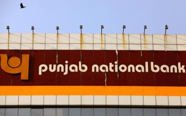 A bird flies past the logo of Punjab National Bank installed on the facade of its office in Mumbai