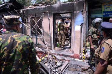 Sri Lanka's Special Task Force and Police officers stand guard near a burnt house after a clash between  two communities in Digana, central district of Kandy