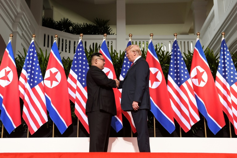 Kim handshakes with Trump-afp