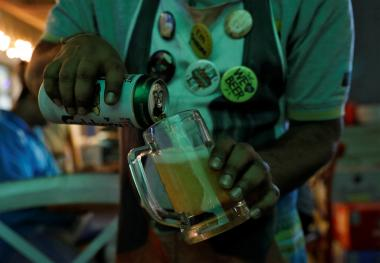 A waiter pours Carlsberg beer at a pub in Mumbai