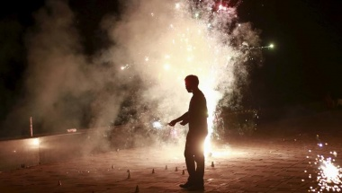 A man lights firecrackers while celebrating the Hindu festival of Diwali, the annual festival of lights in Mumbai