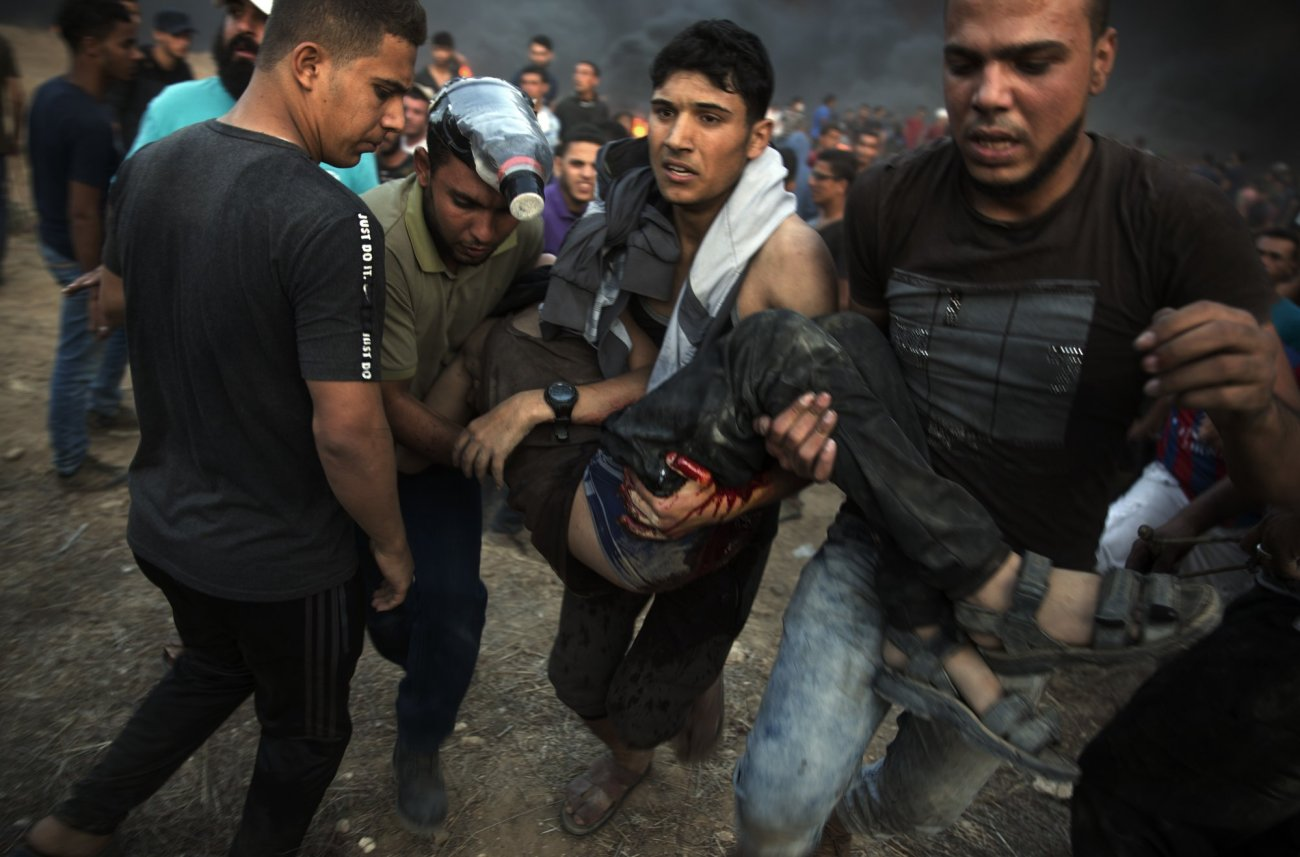 palestinian protesters evacuate wounded man shot by Israeli troops-reuters