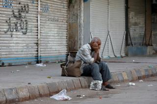 A man sits with his belongings as he waits for transport in front of closed shops during a protest in Karachi