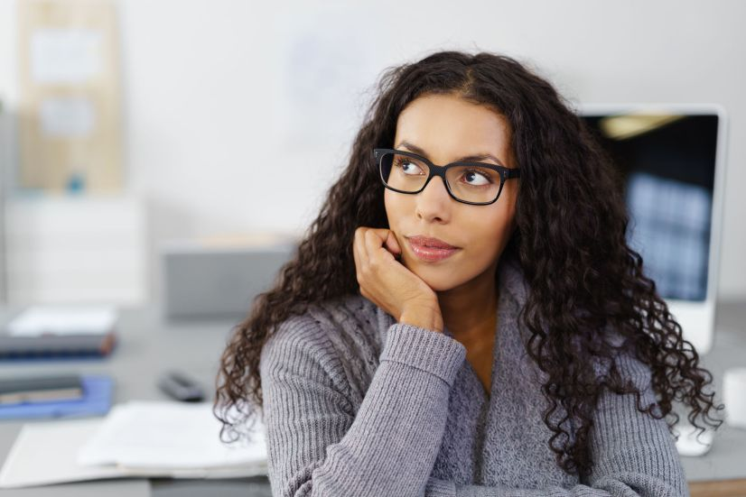 business woman sitting at her desk in the office with her chin on her hand looking up in thoughts