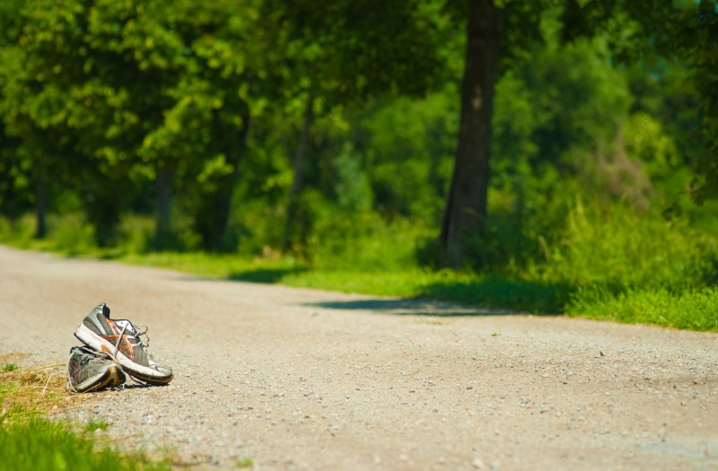 Discarded running shoes next to a dirt track