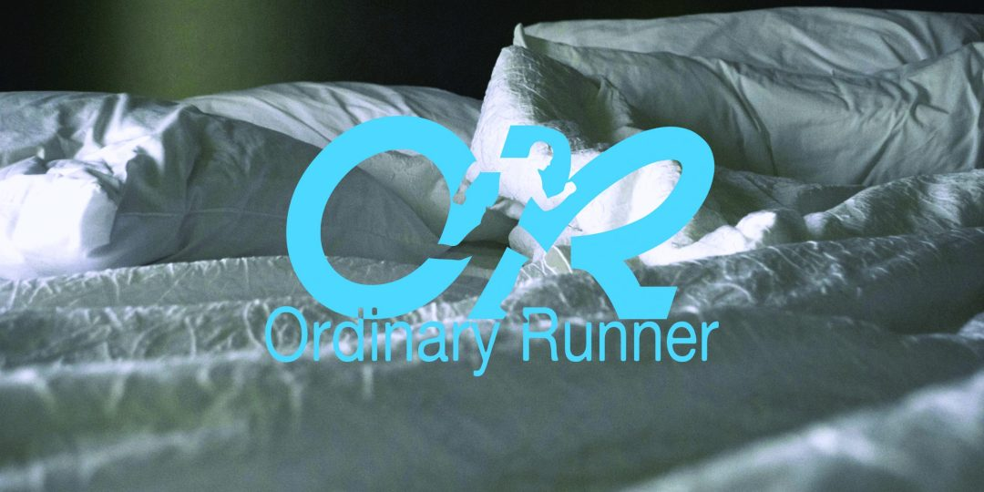 Close up of an unmade bed overlaid by the Ordinary Runner logo