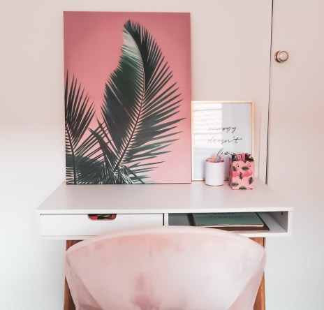 White desk with a pink palm tree print and a small black and white quote saying energy doesn't lie. Desk is clean ready for the semester to start