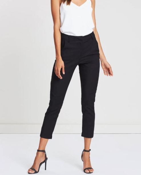 female modelling black pants and a white top
