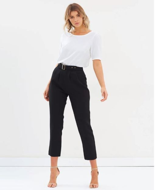 white blonde female model wearing a white shit and black pants