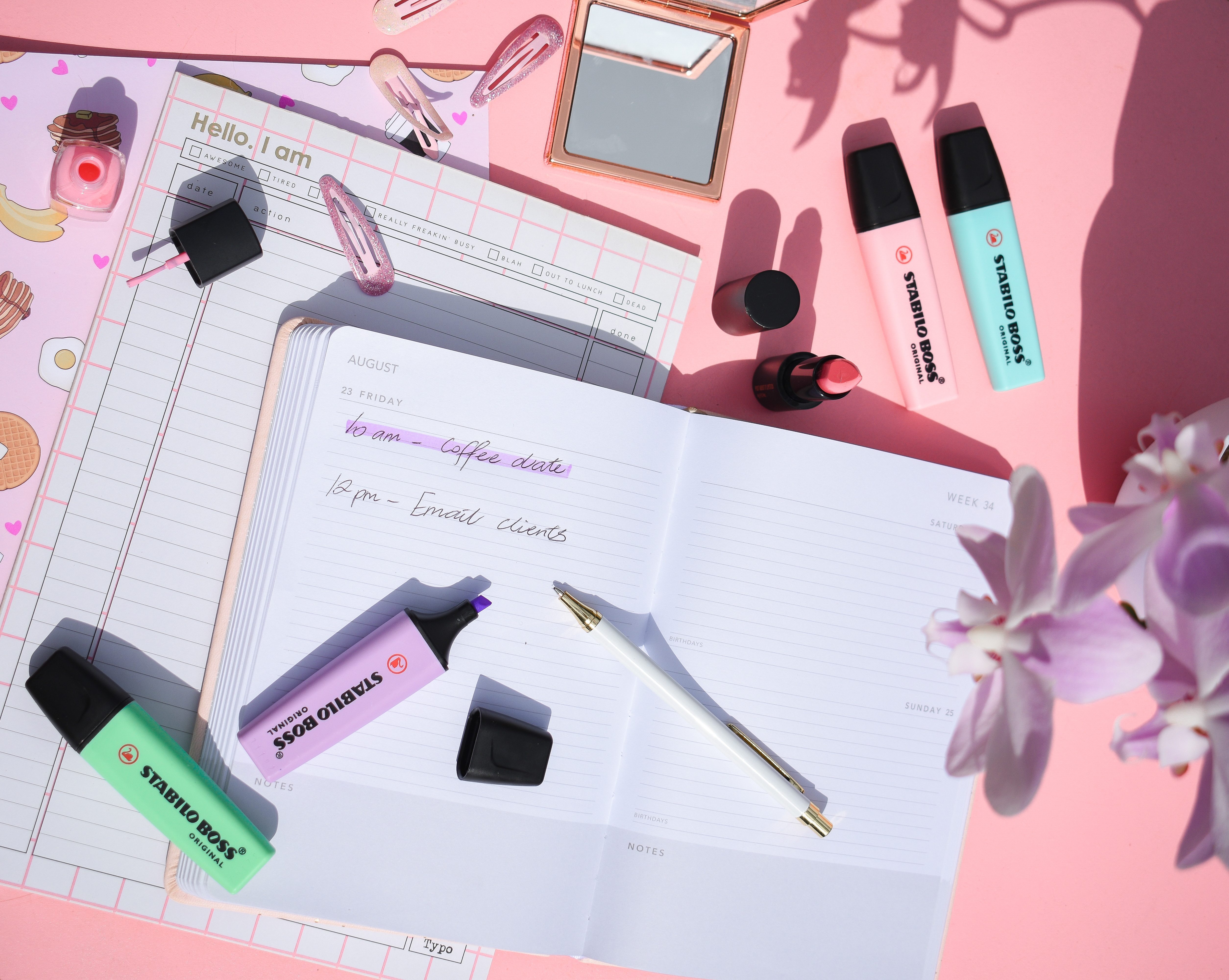 pink table with an open notebooks and pastel stabilo boss highlighters and pens
