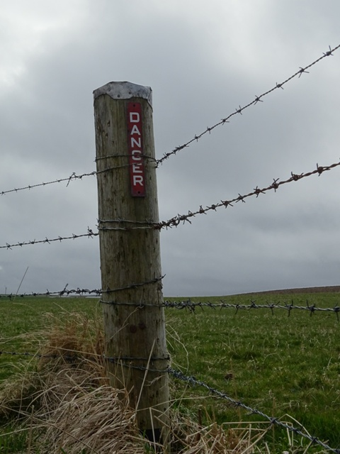 Fence post with danger on it and barbed wire credit Bell