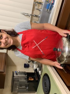 Nicole standing next to the stove. She is holding a pot with both hands out in front of her