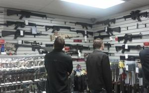 Customers view rifles on display at a gun shop in LA