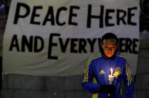 Runner holds candle and flower at vigil