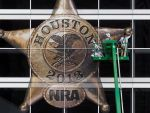 Workers put up the NRA logo in Houston's George Brown Convention Center