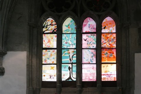 The original windows have been removed for restoration. These paper designs were created by students from a local art college.