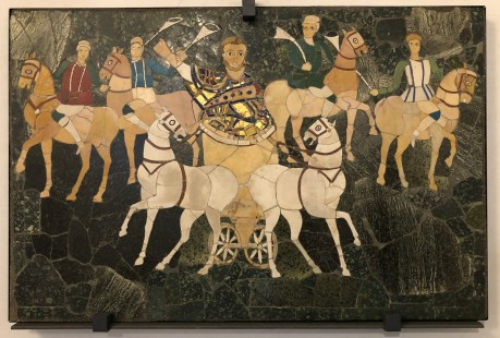 "Two-horse chariot bearing the presiding magistrate at a pompa circensis (""circus parade""). Opus sectile is an art technique popularized in the ancient and medieval Roman world where materials were cut and inlaid into walls and floors to make a picture or pattern. Common materials were marble, mother of pearl, and glass."