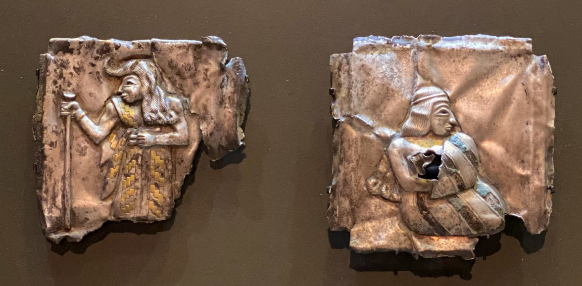 Pair of Silver Plaques depicting a man holding a staff, wearing a belted robe with zigzag pattern and a seated woman wearing a striped dress. Southeastern Iran, early 2nd millennium BCE Silver inlaid with gold and copper.