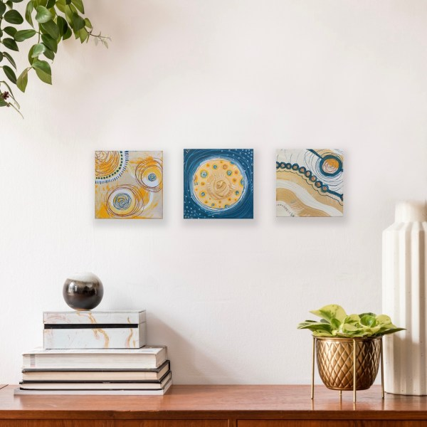 set abstract paintings on wall above shelf