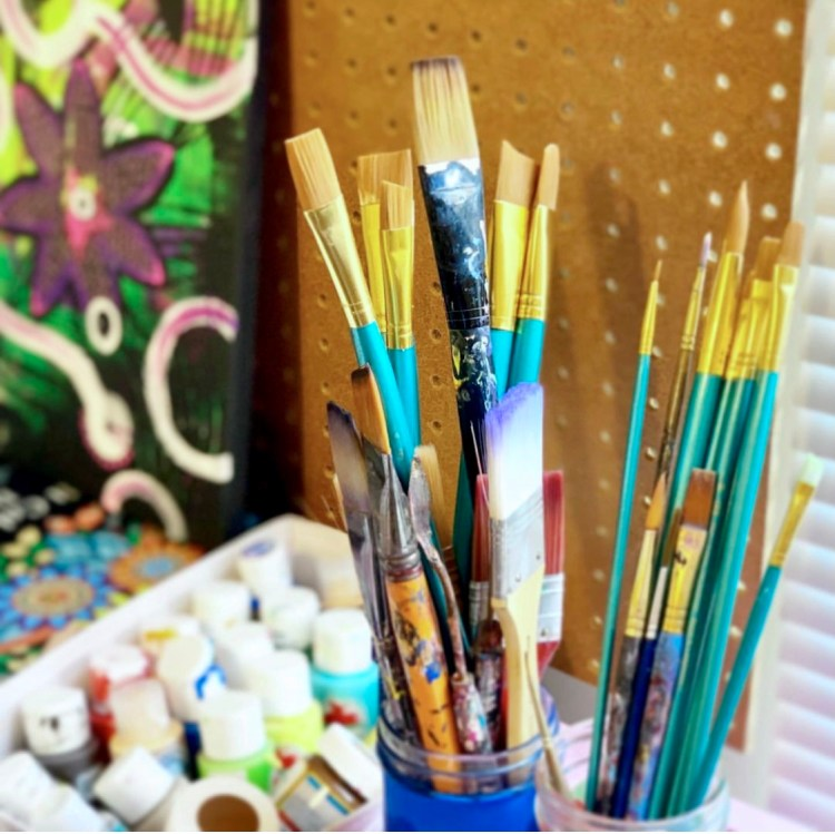 well used assortment of paintbrushes for acrylic painting