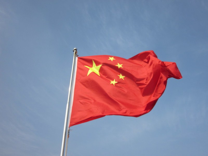 The Chinese flag (red, with one large yellow star and four smaller stars surrounding it in the left corner) flaps against a cloudy sky.